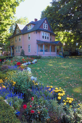 This is a picture of a house with multiple varieties of flowers in the front yard